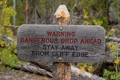 Warning sign dangerous drop ahead stay away from cliff edge. Rustic wood warning sign dangerous drop ahead stay away from cliff edge royalty free stock photography