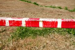 Warning sign, detail of red and white sign barrier on green grass in nature, close up. Transport and traffic regulation. Old fence made and white and red royalty free stock images