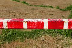 Warning sign, detail of red and white sign barrier on green grass in nature, close up. Transport and traffic regulation. Old fence made and white and red royalty free stock photography