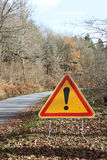 Warning Sign Exclamation Mark. A triangular yellow traffic warning sign stands alongside a rural road. The exclamation mark is generic and can signify multiple royalty free stock photos