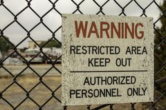 Warning sign on a chain link fence royalty free stock images