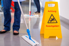 Warning sign in front of cleaning crew Stock Photo