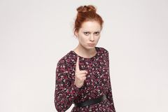 Warning sign. Ginger woman looking at camera with serious face a Stock Images
