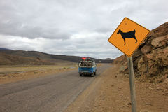 Warning sign for goats on road and vintage van driving, Patagonia, Argentina. Warning sign for goats on road and vintage van driving, Neuquen, Patagonia Stock Image
