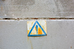Warning sign on a gray wall. Old rusted warning sign on a gray concrete wall stock photography