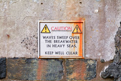 Warning sign on harbour wall. Waves sweep over breakwater in heavy seas - Keep well clear Royalty Free Stock Photography