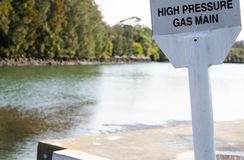 Warning sign for High-pressure gas main near the river. royalty free stock images