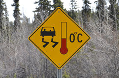 Warning sign on highway. Road sign warning of slippery and icy conditions at freezing temperatures at Alaska Highway (Alcan), Canada royalty free stock image