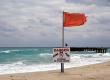 Warning Sign (Horizontal). Danger sign on a beach in Boca Raton, Florida, with rough surf and stormy skies in the background Royalty Free Stock Photo