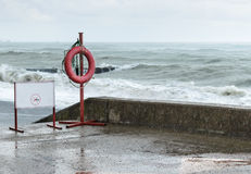 Warning sign and a life buoy. On the waterfront in the storm stock images