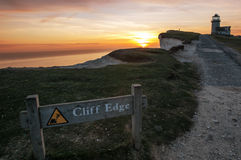 Warning sign with lighthouse at Beachy Head at sunset Stock Photo