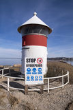 Warning sign and lighthouse. Old red and white lighthouse and building site warning sign close to Assens new harbor bridge in Denmark Stock Image