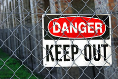 Warning sign on metal fence Stock Photos