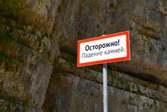 Warning sign in the mountains about the rockfall. Translation from Russian. Caution! Falling stones Stock Image