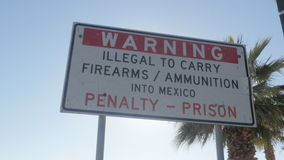 Warning Sign Near the US and Mexico Border. 4K shot of a warning against bringing firearms or ammunition into Mexico near the US and Mexico border on a sunny day stock footage