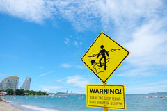 A warning sign plate. A yellow warning sign plate warns about to beware jellyfish royalty free stock image