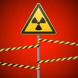Warning sign on a pole and warning bands. Sign of radiation hazards. Vector illustration. Stock Photography