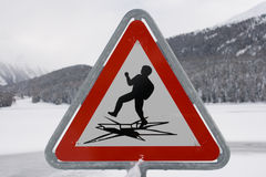Warning sign post. Sign post alerting against the possibility of ice breaking, St. Moritz, Switzerland Royalty Free Stock Image