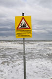 Warning sign on post near the sea Royalty Free Stock Photography