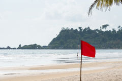 Warning sign of a red flag at a beautiful beach with a blue sky Stock Photo