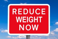 Warning sign REDUCE WEIGHT NOW. Red and white warning sign REDUCE WEIGHT NOW in front of blue sky, symbol for the health risks or dangers of overweight stock photo