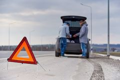 Warning sign on the road on a blurred background of people near the car stock images
