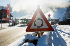Warning  sign on road covered by snow at mountains Stock Photography