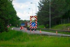 A warning sign on the road runs ahead. Road sign. Road repair.  stock photos