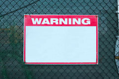 Warning Sign safety caution with blank white message at construction site grid boundary. Stock Images