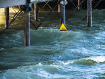 Warning sign in the sea under a pier Stock Photography