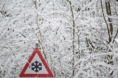 Warning sign shows danger of ice and snow at street Royalty Free Stock Image
