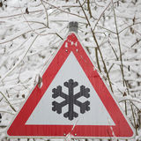 Warning sign shows danger of ice and snow at street Stock Image