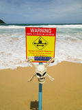 Warning sign with skull. strong currents. Yellow sign post with skull is warning of dangerous currents on a beach  in Phuket, Thailand Royalty Free Stock Photo