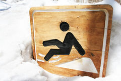 Warning sign slippery on snow. Wood warning sign slippery on snow royalty free stock photo