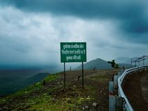Warning Sign on Sloped Mountain Roads of India. Warning Sign on Sloped Mountain Roads or Ghaat Section of India. In Background Dramatic Dark Rain Clouds and stock photo