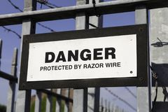A warning sign stating Danger Protected by Razor Wire mounted on. Railings outside a business in Warrington May 2018 Royalty Free Stock Photos