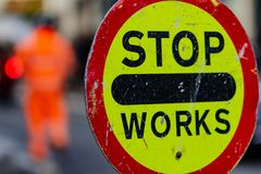 Warning sign Stop Works and a man in orange working in background on the street, photographed with shallow depth of field royalty free stock photo