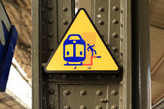 Warning sign: train. Triangle yellow sign warning of the danger of standing near the edge of the platform Stock Image