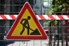 The warning sign `under construction` is attached to a metal mesh fence with a red and white striped signal tap. E Royalty Free Stock Images