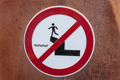 Warning sign on a wall. With the meaning not to jump down from the wall Royalty Free Stock Image