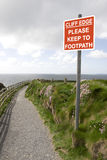 Warning sign among wild flowers along a cliff path Stock Photography