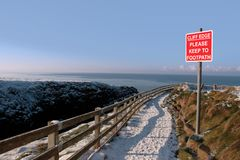 Warning sign on a winter snow cliff walk Royalty Free Stock Photo