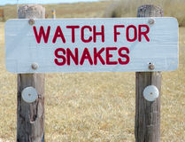 Warning Sign. Wooden sign in a park with the message Watch For Snakes painted on it Royalty Free Stock Photos