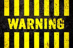 Warning sign with yellow and black stripes painted over cracked concrete wall coarse texture background Stock Photo