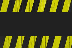 Warning sign with yellow and black stripes painted over cracked wood as border frame with black empty background Royalty Free Stock Photo
