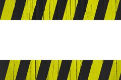 Warning sign yellow and black stripes painted over cracked wood as border frame Royalty Free Stock Images