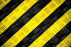 Warning sign yellow and black stripes background painted steel checker plate diamond plate on the floor as texture background. Warning sign yellow and black stock image