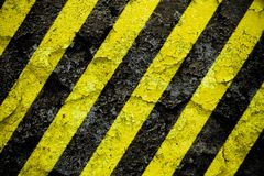 Warning sign yellow and black stripes pattern painted over concrete cement wall facade with peeling cracked paint background. Warning sign yellow and black royalty free stock photography