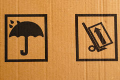 Warning signs. Fragment of a cardboard box with packaging warning signs Stock Image