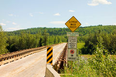 Warning signs at a bridge spanning the fort nelson river. A sturdy wooden bridge as seen in northern british columbia Stock Image
